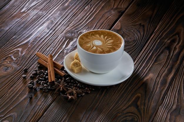 Eine tasse cappuccino mit kaffeebohnen, zimt und braunem zucker auf holztisch