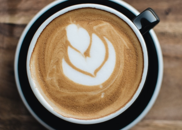 Eine tasse cappuccino mit latte art auf einem hölzernen hintergrund. nahaufnahme.
