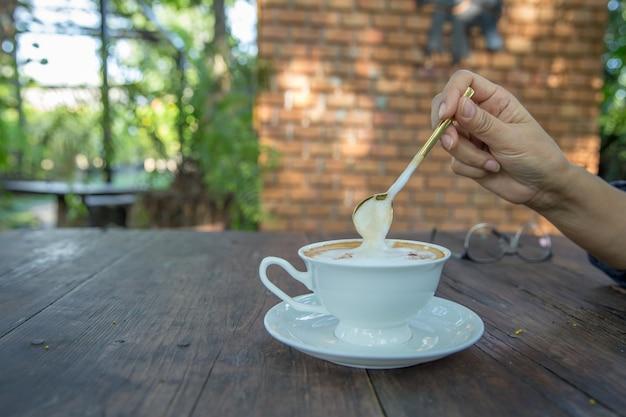 Eine tasse cappuccino mit latte art auf holztisch. wunderschöner schaum, grüne keramikbecher, stilvolle tönung