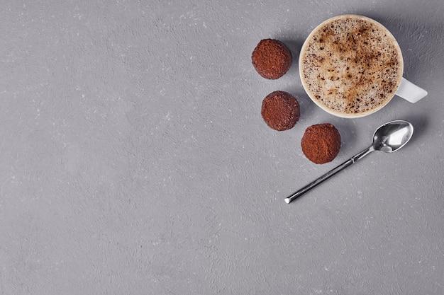 Eine tasse cappuccino mit schokoladenoberteilen.