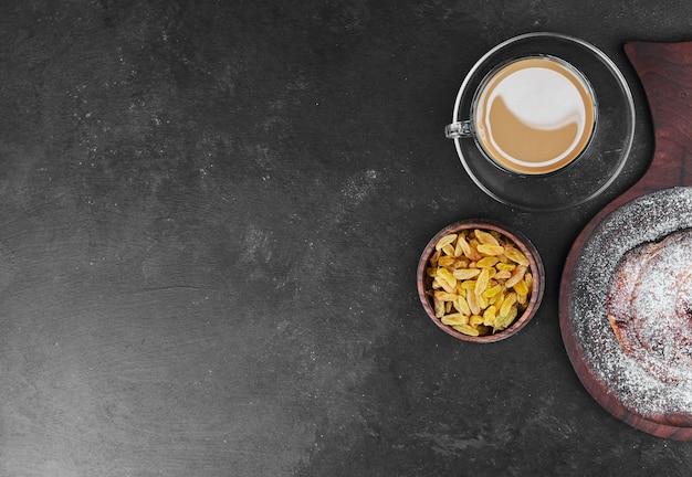 Eine tasse cappuccino mit trockenen früchten und süßem brötchen.