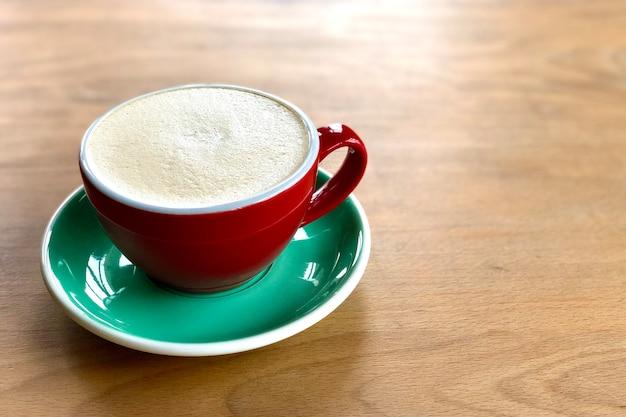 Eine tasse cappuccino, raf-kaffee, auf hölzernem hintergrund. rote keramikschale und grüne untertasse.