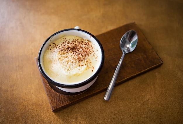 Eine tasse cappuccino steht auf einem holztisch und steht für einen löffel