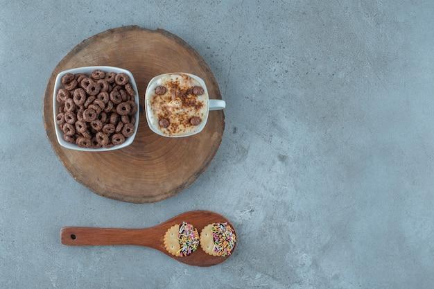 Eine tasse cappuccino und eine schüssel maisring auf einem brett neben dem löffel auf blauem hintergrund.