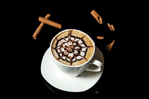 Eine tasse cappuccino und zimtstangen auf der tischansicht