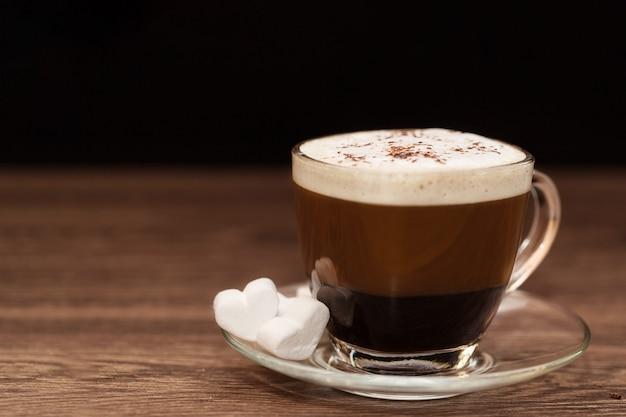 Eine tasse duftenden kaffee mit milch und einem herzförmigen marshmallow zum frühstück auf einem holztisch