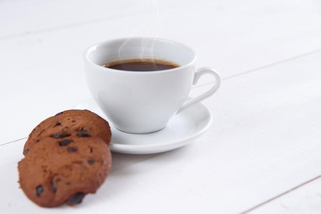 Eine tasse duftenden kaffees mit milch und keksen auf dem weißen hintergrund. shortbread cookies mit schokoladenscheiben und weißer tasse kaffee.