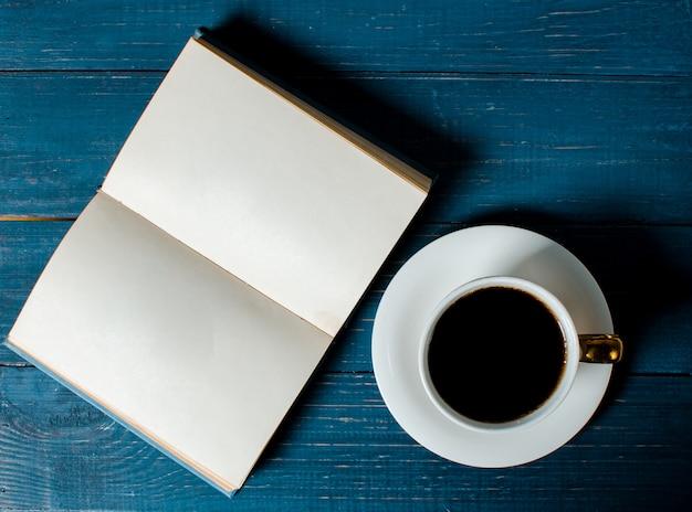 Eine tasse duftenden kaffees und ein buch liegen auf einem hölzernen hintergrund.