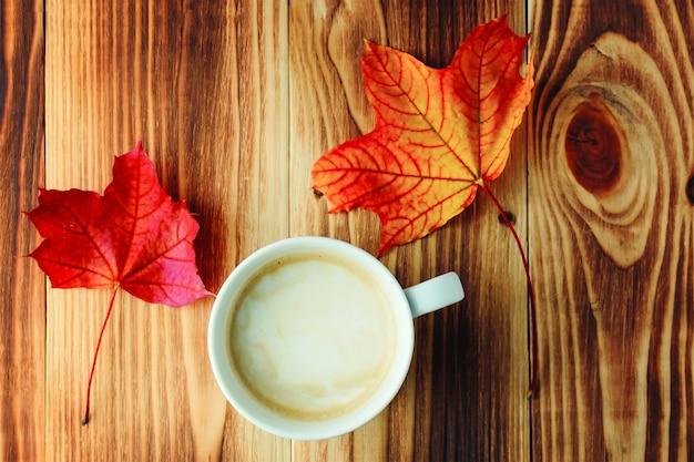 Eine tasse duftender kaffee und zwei bunte ahornblätter im herbst