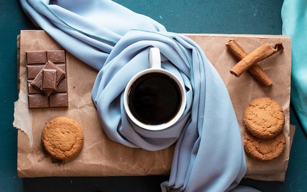 Eine tasse dunklen espresso mit zimt, keksen und einem schokoriegel. ansicht von oben.