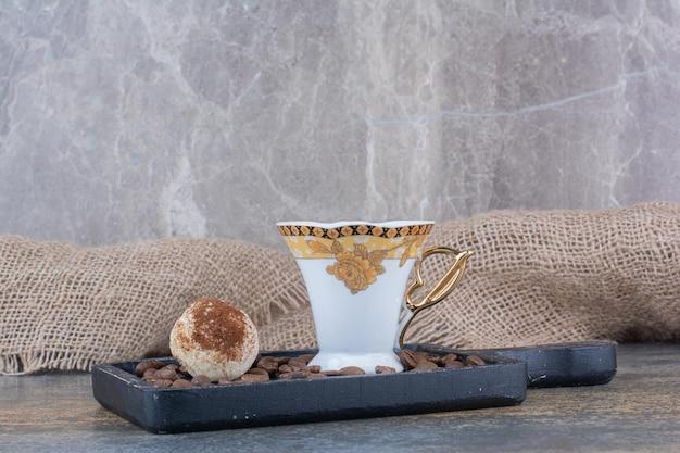 Eine tasse dunklen kaffee mit keks auf dunklem brett. foto in hoher qualität