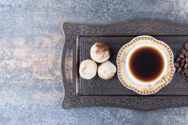 Eine tasse dunklen kaffee mit keks auf dunklem brett.