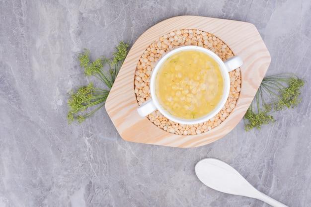 Eine tasse erbsenbohnensuppe auf ungekochten bohnen in einer holzplatte.