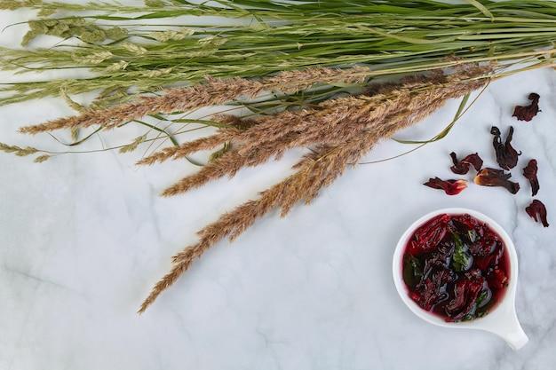 Eine tasse erfrischender obst-karkade-tee mit minze und einem strauß wilder kräuter auf einem leuchttisch. ein erfrischendes getränk in der sommerhitze