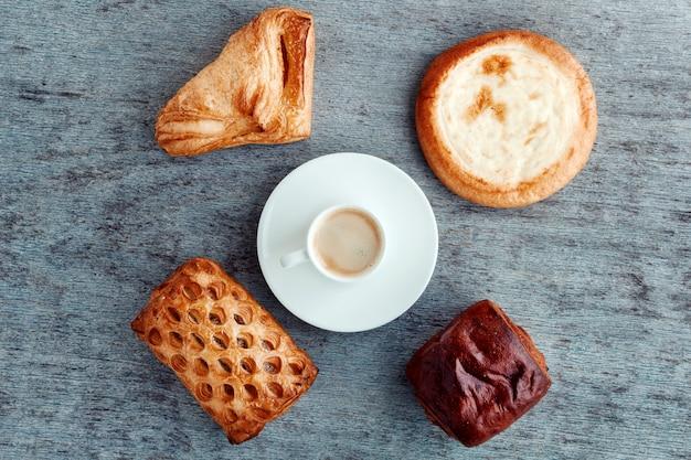 Eine tasse espresso auf einer untertasse, brötchen und kuchen auf einem hölzernen backgr