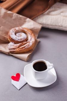 Eine tasse espresso auf einer untertasse und ein schichtbrötchen
