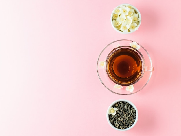 Eine tasse frisch gebrühten grünen tee und eine schüssel jasminblüten auf einem rosa tisch.