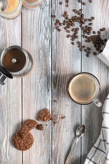 Eine tasse frisch gebrühten kaffee mit schokoladen-shortbreads, gerösteten kaffeebohnen und moka-topf auf einer holzoberfläche. kinfolk-stil. flach legen