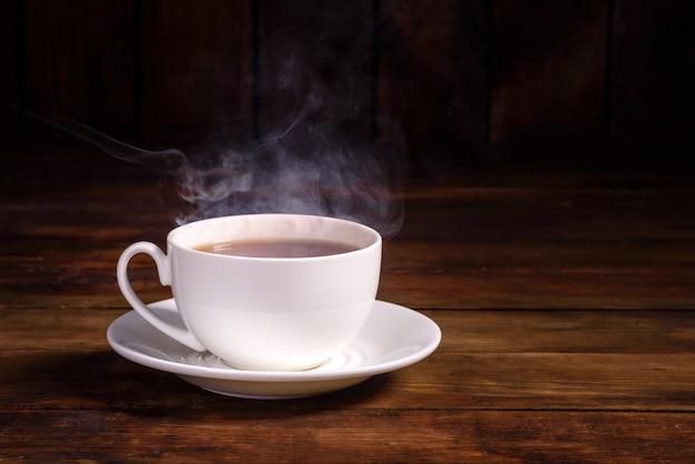 Eine tasse frisch gebrühten schwarzen tee, der dampf entweicht, warmes, weiches licht