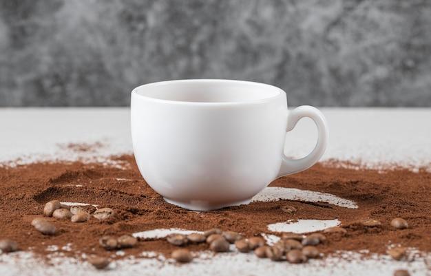 Eine tasse getränk auf dem kaffeepulver.