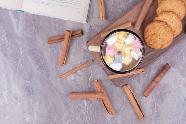 Eine tasse getränk mit marshmallows und haferkeksen