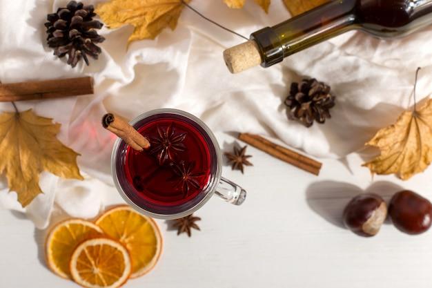Eine tasse glühwein mit gewürzen, flasche, schal, gewürzen, trockenen blättern und orangen auf dem tisch. herbststimmung, methode, um in der kälte warm zu halten, copyspace.
