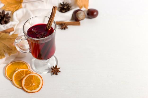 Eine tasse glühwein mit gewürzen, schal, gewürzen, trockenen blättern und orangen auf dem tisch. herbststimmung, eine methode, um in der kälte warm zu halten, copyspace.