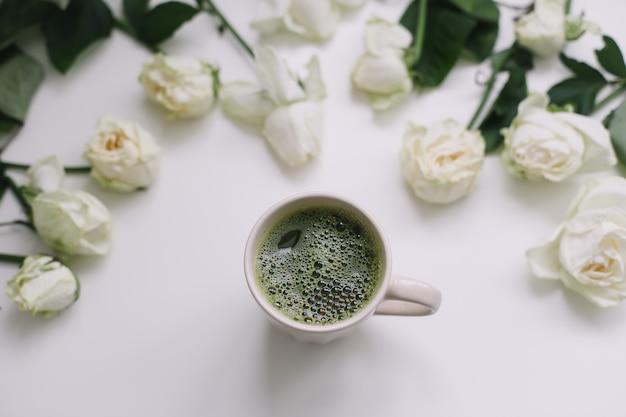 Eine tasse grüner matcha-tee mit weißen rosen auf weißer ansicht von oben