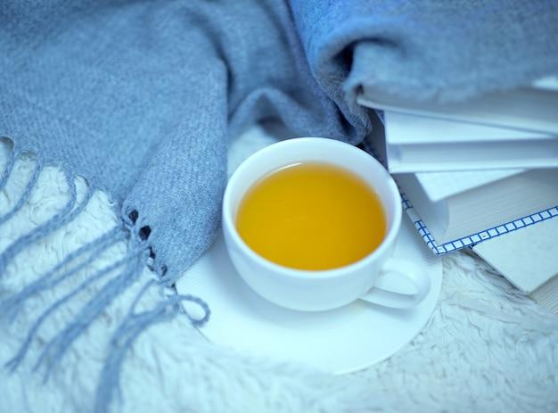 Eine tasse grüner tee, bücher und eine warme wollstrickdecke auf dem bett.