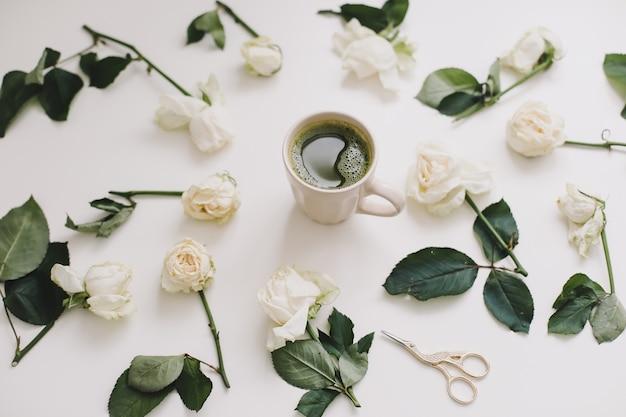 Eine tasse grüner tee mit weißen rosen auf weißer ansicht von oben. flatlay, draufsicht, kopierraum.