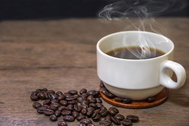 Eine tasse heiße espresso-kaffeetassen und geröstete kaffeebohnen, die auf holzbodenhintergrund gelegt werden