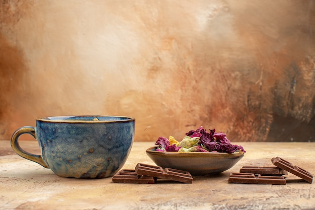 Eine tasse heiße kräuterteeblumen und schokoriegel auf gemischtem farbtisch