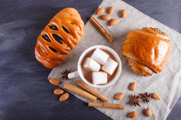 Eine tasse heiße schokolade mit marshmallow, brötchen, mandeln und gewürzen