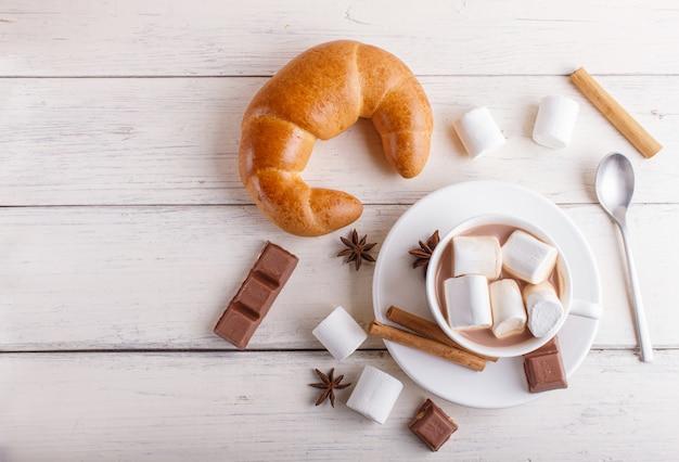 Eine tasse heiße schokolade mit marshmallow, croissant und gewürzen