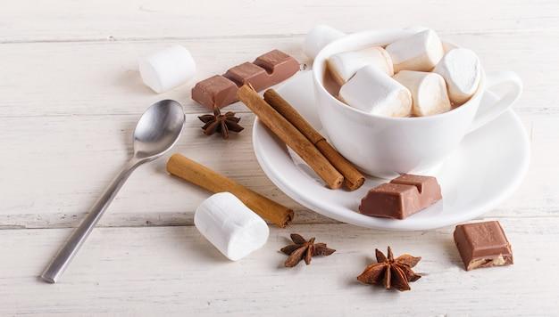 Eine tasse heiße schokolade mit marshmallow und gewürzen