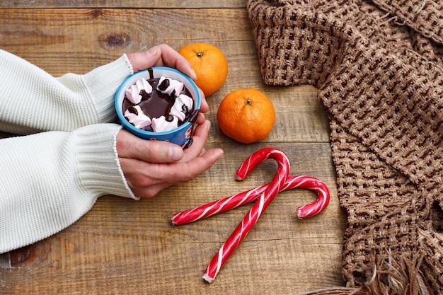 Eine tasse heiße schokolade und eibisch. bild auf einem hölzernen hintergrund mit tangerinen, swee