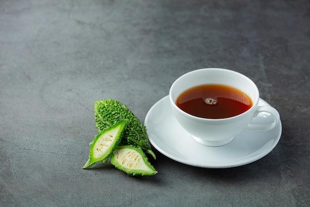 Eine tasse heißen bitteren kürbistee mit geschnittenem rohem bitterem kürbis auf dunklem boden