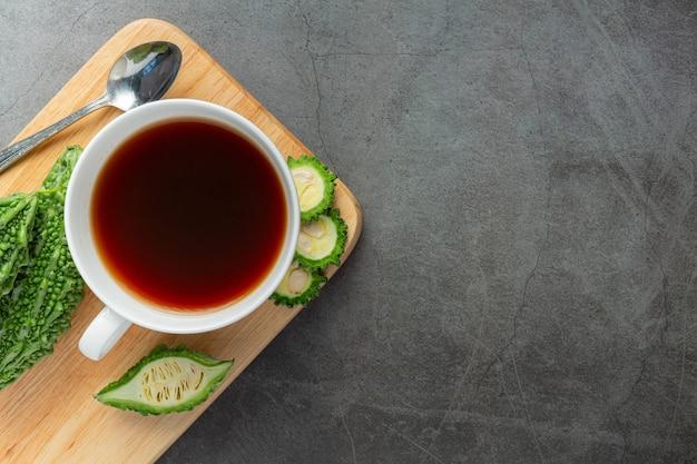 Eine tasse heißen bitterkürbistee mit geschnittenem rohem bitterkürbis auf holzschneidebrett legen