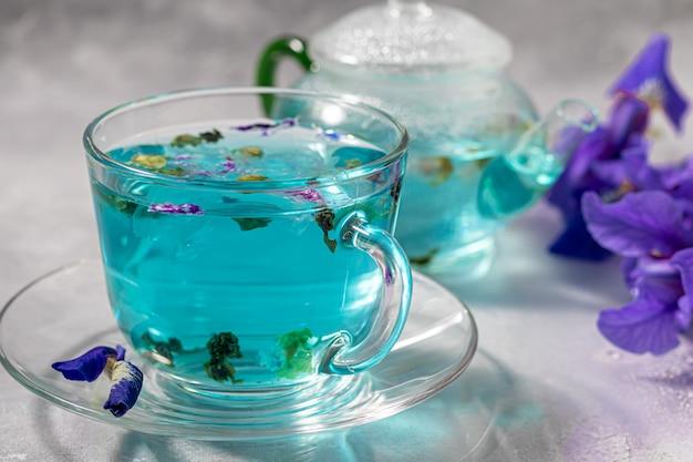 Eine tasse heißen, blauen tee mit erbsenblüten. blaue erbsen. für gesundes trinken, entgiftung des körpers. grauer tisch.