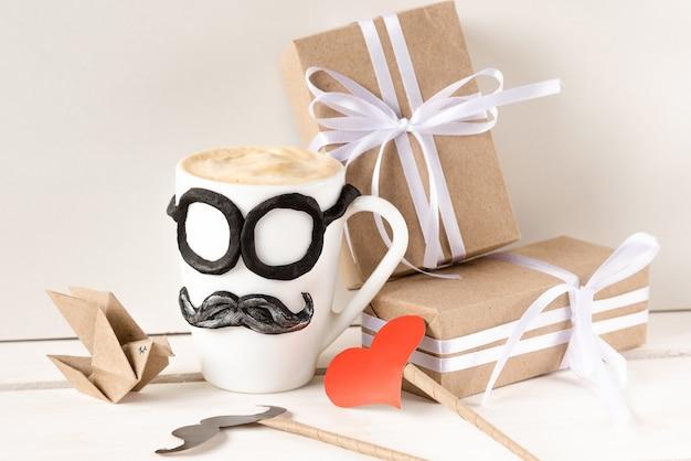 Eine tasse heißen cappuccino und geschenke für den vatertagsurlaub.