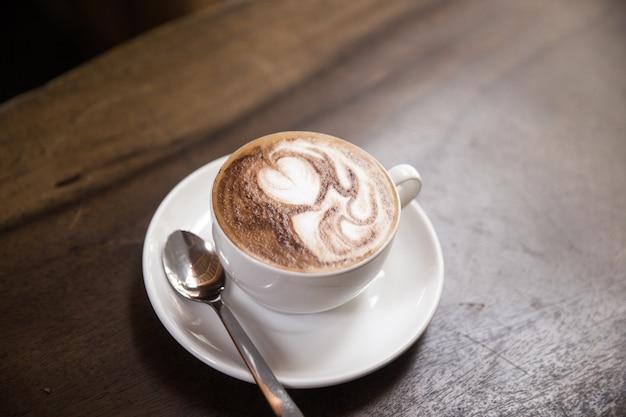 Eine tasse heißen cappucino steht auf dem holztisch. es ist eine kunst auf dem latte.