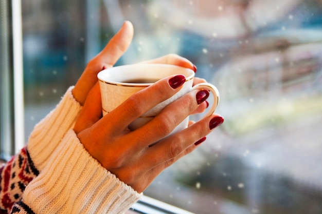 Eine tasse heißen kaffee in händen mit einer schönen maniküre. winterstimmung