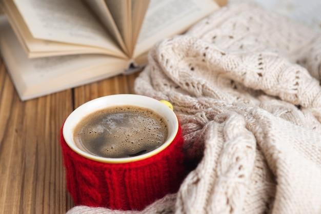 Eine tasse heißen kaffee mit einem warmen winterpullover und einem buch auf dem tisch. winter-komposition