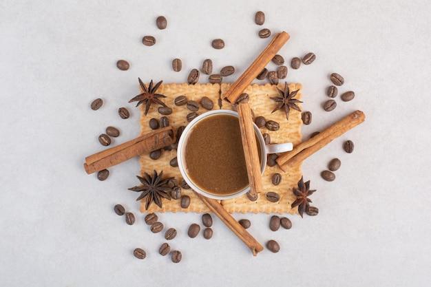 Eine tasse heißen kaffee mit sternanis und zimtstangen auf crackern