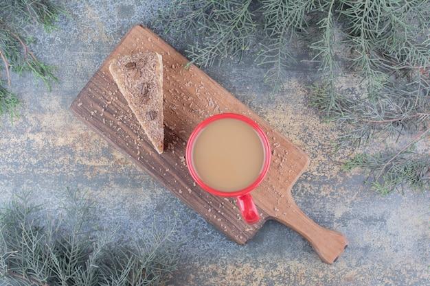 Eine tasse heißen kaffee mit stück kuchen auf marmorhintergrund. foto in hoher qualität