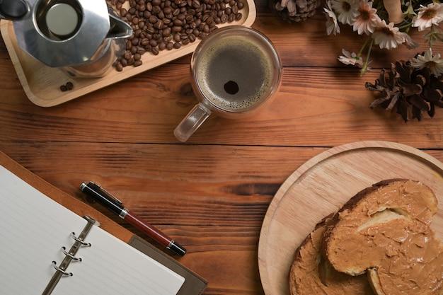 Eine tasse heißen kaffee und erdnussbutter-sandwich auf holztisch.