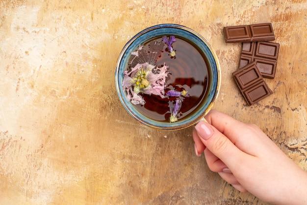 Eine tasse heißen kräutertee und schokoriegel auf gemischtem farbtisch