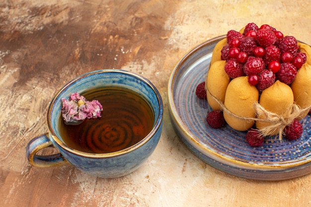 Eine tasse heißen kräutertee weichen kuchen mit früchten auf gemischten farbtisch