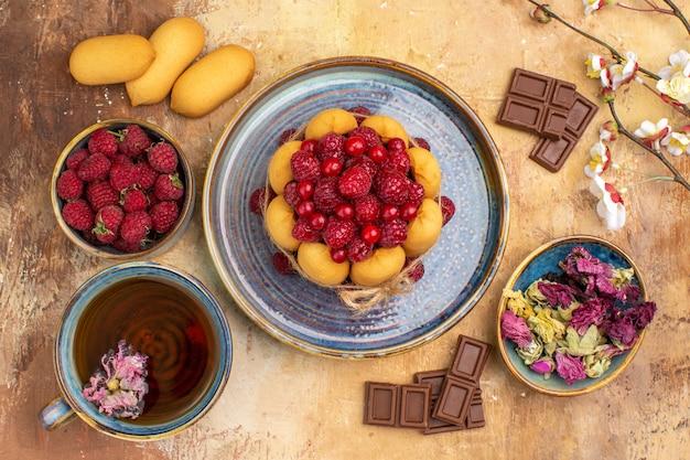 Eine tasse heißen kräutertee weichen kuchen mit früchten schokoriegel auf gemischten farbtisch