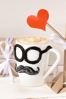 Eine tasse heißen latte und vatertagsgeschenke.